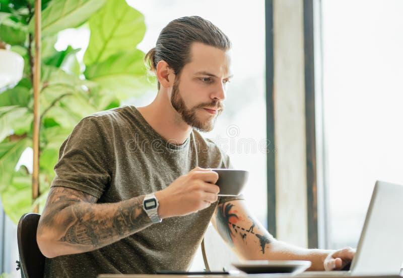 Hombre concentrado del inconformista con el funcionamiento barbudo en el ordenador portátil y café o té de consumición en la cafe imagen de archivo libre de regalías