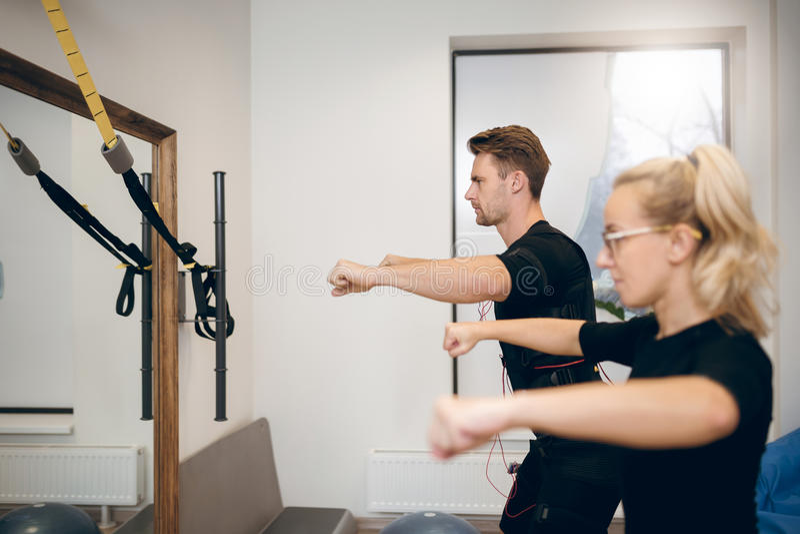 Hombre concentrado que ejercita con el instructor personal imagen de archivo