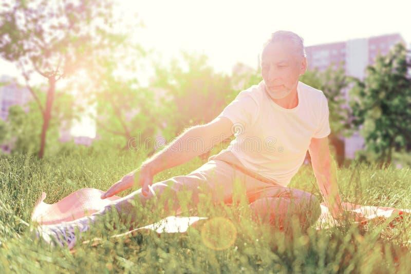 Hombre concentrado que estira hacia fuera en el cojín de tierra fotografía de archivo