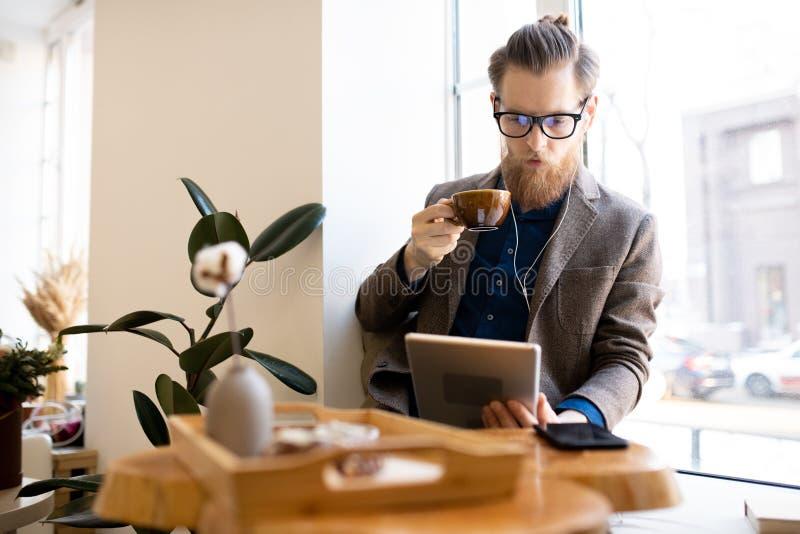 Hombre concentrado que lee el libro en línea en café fotos de archivo