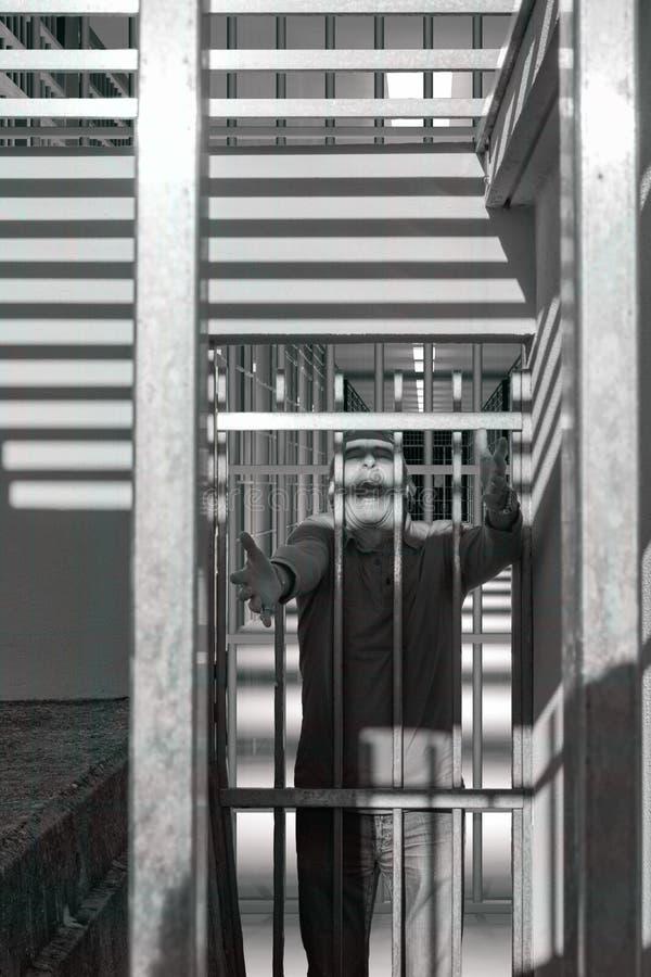 Hombre condenado detrás de barras de una puerta de la prisión, gritando en miedo y cólera imagen de archivo