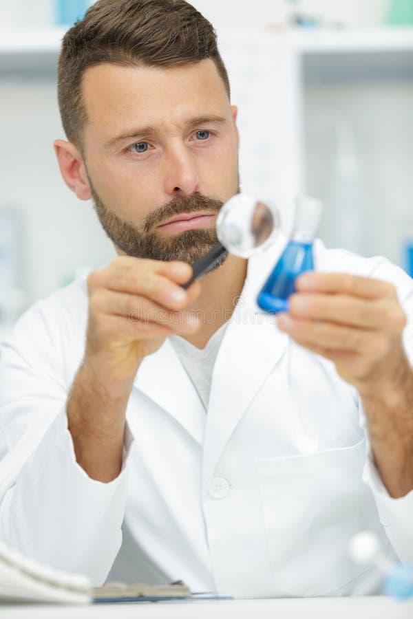 Hombre confiado en paños protectores con el líquido azul fotografía de archivo libre de regalías