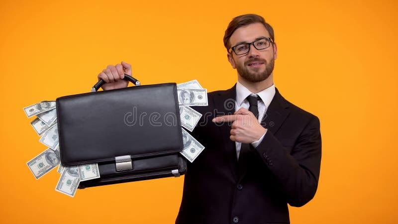 Hombre confiado en traje que se?ala en la cartera por completo de los d?lares, renta crowdfunding foto de archivo libre de regalías