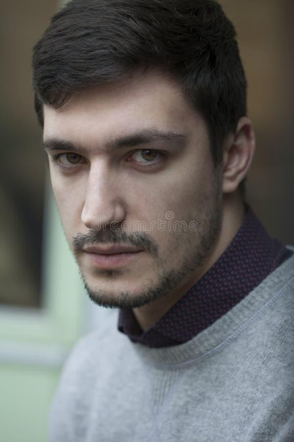 Hombre confiado joven en el suéter que parece muy serio fotografía de archivo