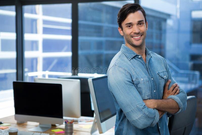 Hombre confiado que se coloca en oficina imagen de archivo libre de regalías