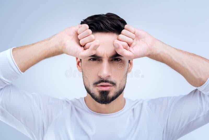 Hombre confiado serio que agrupa los puños mientras que mira derecho fotografía de archivo libre de regalías