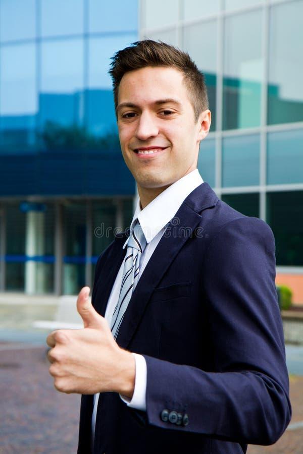 Hombre confiado sonriente de los jóvenes que hace los pulgares para arriba imagenes de archivo
