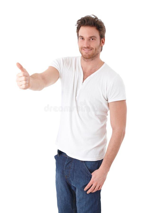 Hombre confidente que muestra el pulgar para arriba que sonríe fotografía de archivo libre de regalías