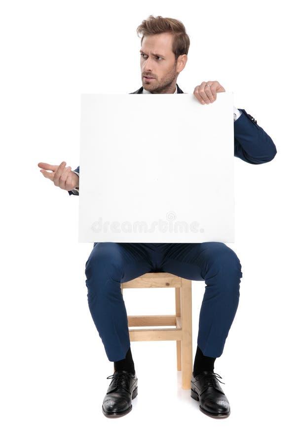 Hombre confuso asentado que sostiene una cartelera en blanco en sus manos fotos de archivo libres de regalías