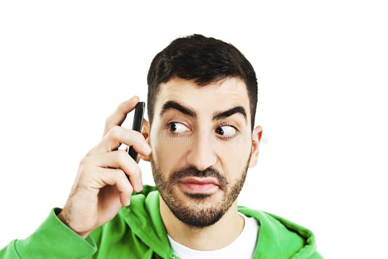Hombre confuso con el teléfono móvil imagen de archivo libre de regalías