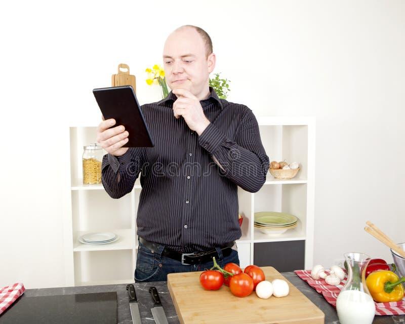 Hombre confuso que lee su tableta mientras que cocina imagen de archivo