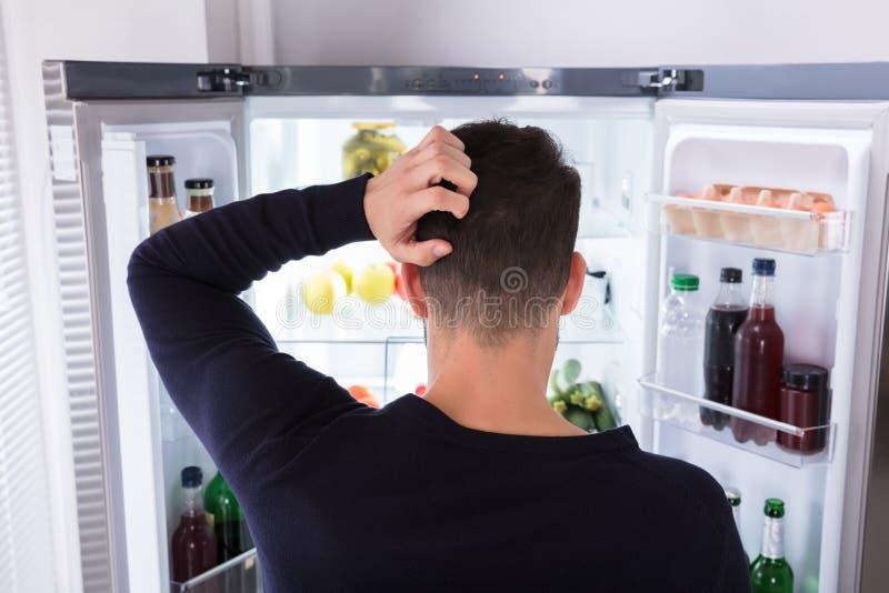 Hombre confuso que mira la comida en refrigerador fotografía de archivo