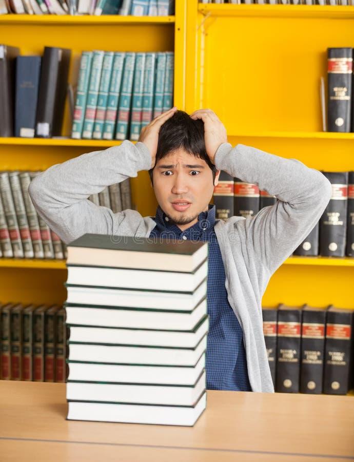 Hombre confuso que mira los libros apilados en biblioteca fotografía de archivo