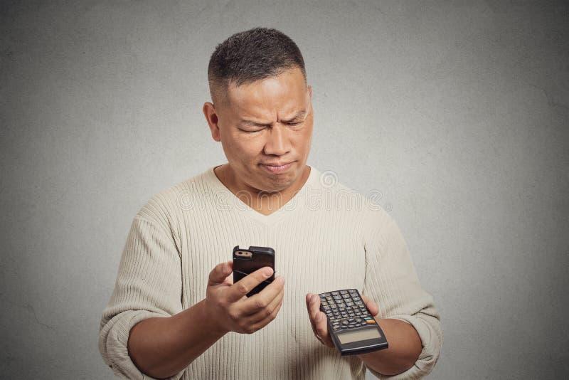 Hombre confuso que mira su teléfono elegante que sostiene la calculadora imagen de archivo