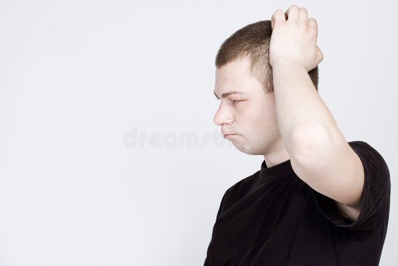 Hombre confuso que rasgu?a la pista Un hombre joven confuso está rasguñando su cabeza imágenes de archivo libres de regalías