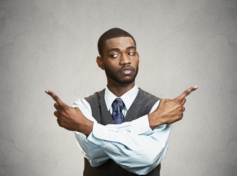 Hombre confuso que señala en dos diversas direcciones fotos de archivo