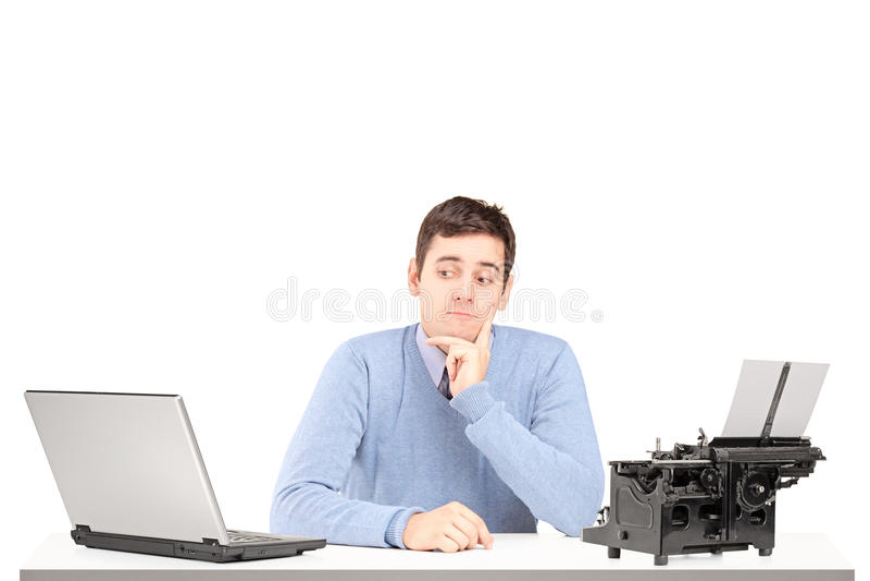 Hombre confuso que se sienta en un escritorio con un ordenador portátil y un machin que mecanografía fotos de archivo libres de regalías