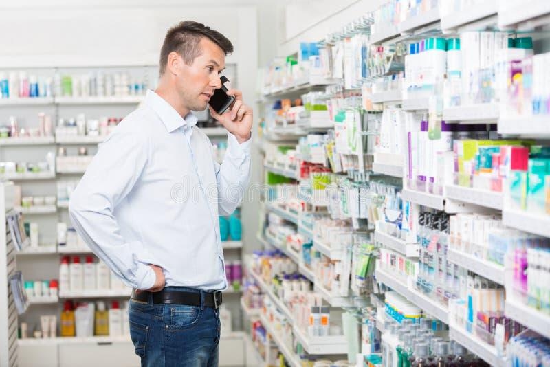 Hombre confuso que usa el teléfono móvil en farmacia fotografía de archivo libre de regalías