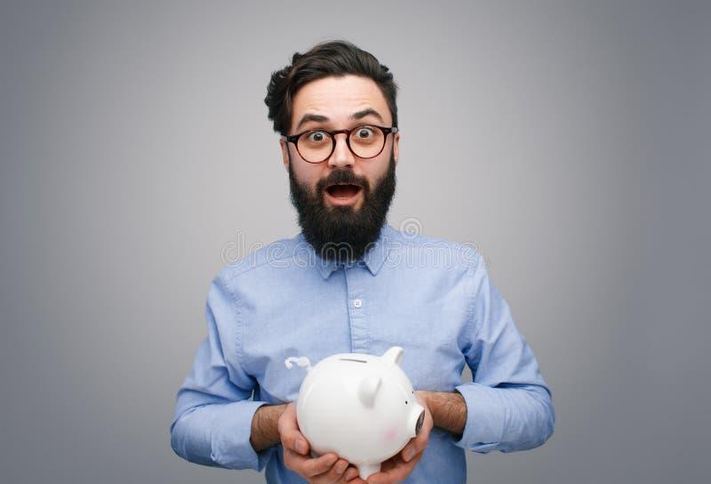 Hombre contento con la hucha en gris fotografía de archivo