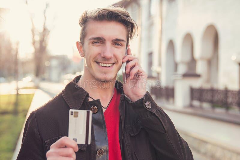 Hombre contento con la tarjeta de crédito que habla en el teléfono imagen de archivo libre de regalías
