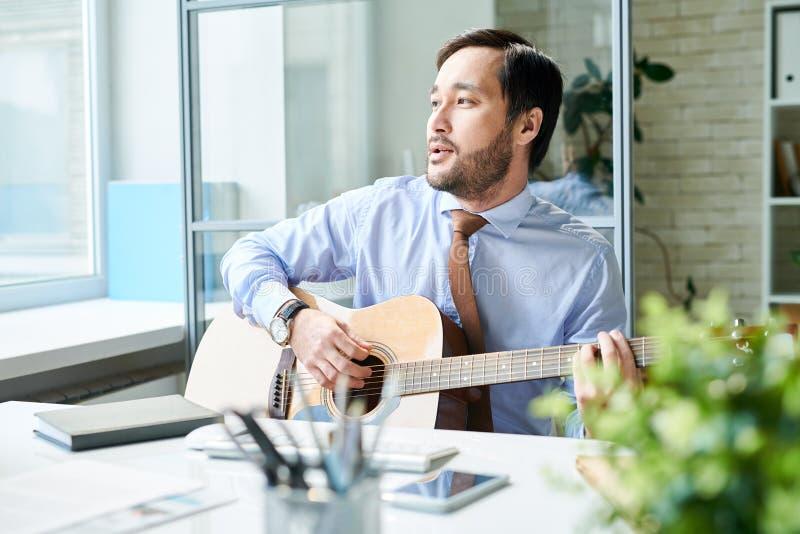 Hombre contento que toca la guitarra en el trabajo fotografía de archivo
