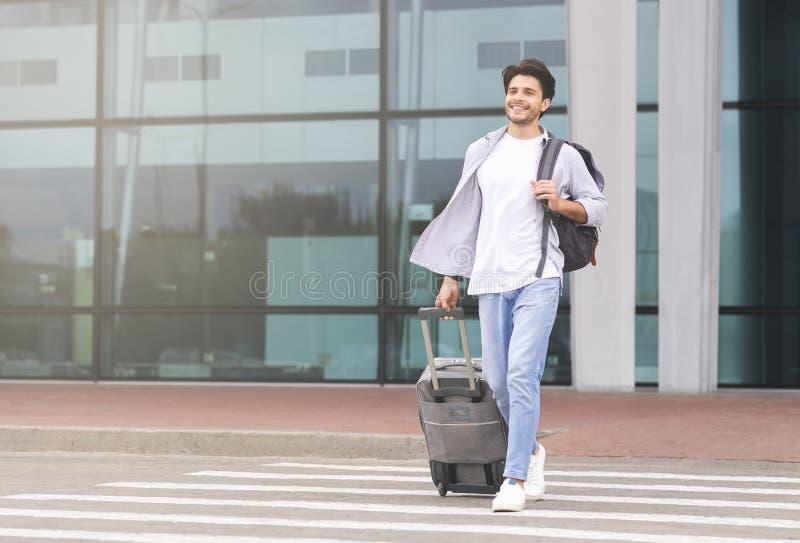 Hombre contento saliendo del edificio del aeropuerto con equipaje fotos de archivo