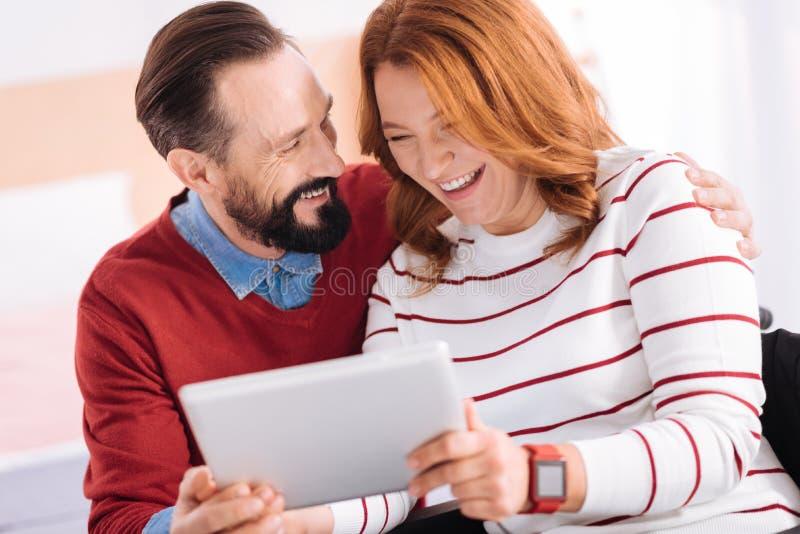 Hombre contento y mujer que ríen mientras que usa una tableta fotografía de archivo
