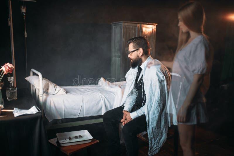 Hombre contra la cama de hospital vacía, alma de la mujer muerta imagenes de archivo