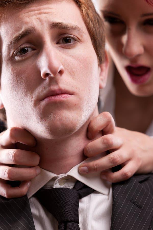 Hombre CONTRA molestias de la mujer en lugar de trabajo imagen de archivo