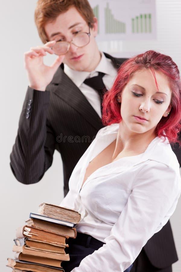 Hombre CONTRA molestias de la mujer en lugar de trabajo imágenes de archivo libres de regalías