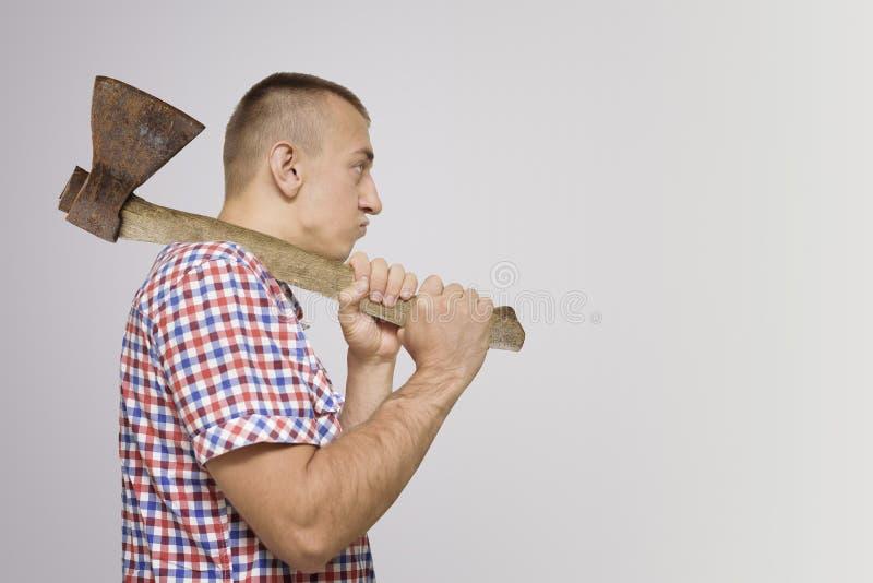 Hombre contrariedad con un hacha en su hombro Fondo blanco imagen de archivo libre de regalías