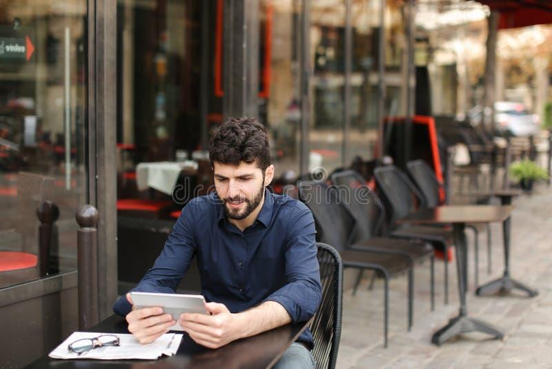 Hombre contrariedad que juega al juego online por la tableta en el café de la calle fotografía de archivo