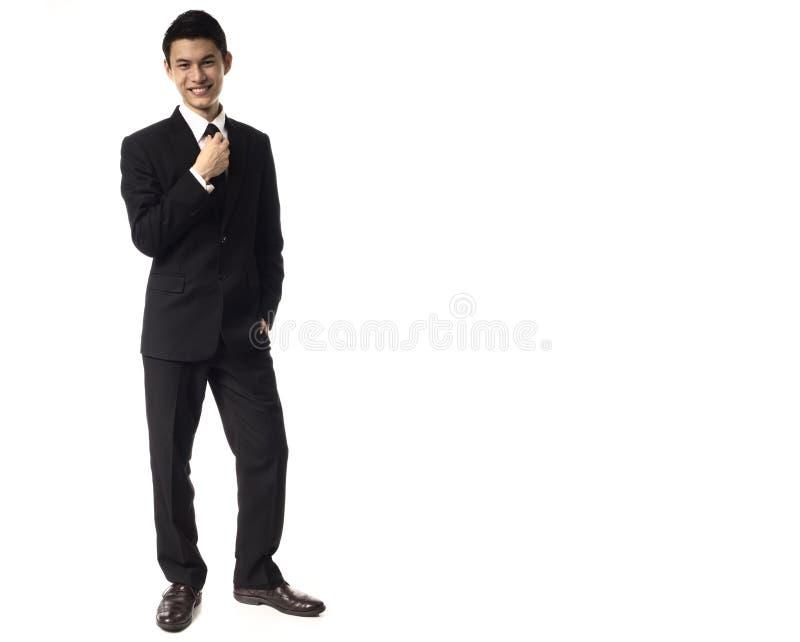 Hombre corporativo asiático joven que ajusta el lazo imagen de archivo libre de regalías