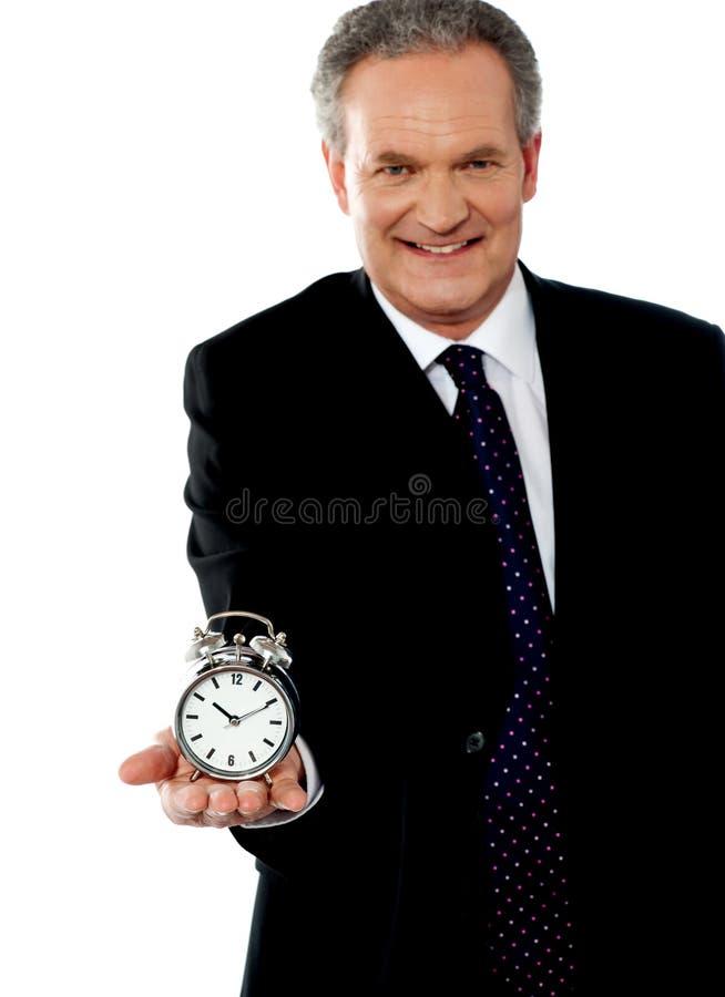 Hombre corporativo que muestra el reloj de alarma fotografía de archivo libre de regalías