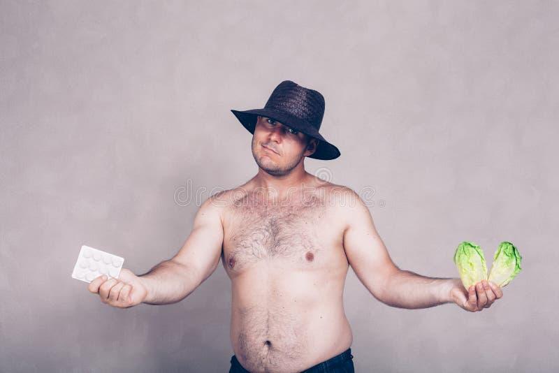 Hombre corpulento desnudo que da los productos farmacéuticos y la verdura fotos de archivo libres de regalías