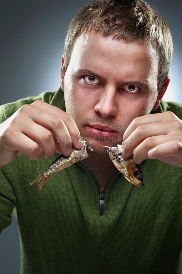 Hombre corpulento hambriento con los pescados foto de archivo