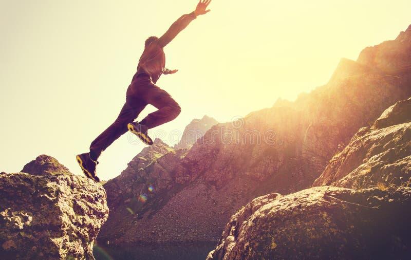 Hombre corriente en las montañas que saltan el acantilado sobre el lago foto de archivo libre de regalías