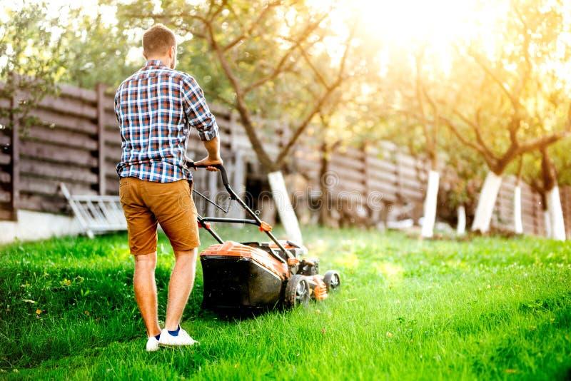 Hombre cortando hierba en su jardín usando una cortadora de césped a gasolina fotos de archivo libres de regalías