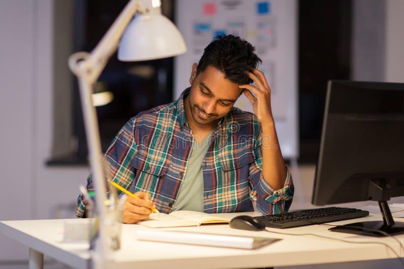 Hombre creativo con el cuaderno que trabaja en la oficina de la noche fotos de archivo