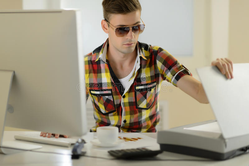 Hombre creativo. Hombres jovenes hermosos en las gafas de sol que se sientan en su wo imagenes de archivo