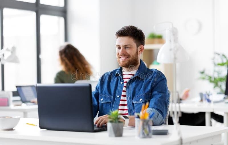 Hombre creativo sonriente con el ordenador portátil que trabaja en la oficina fotografía de archivo