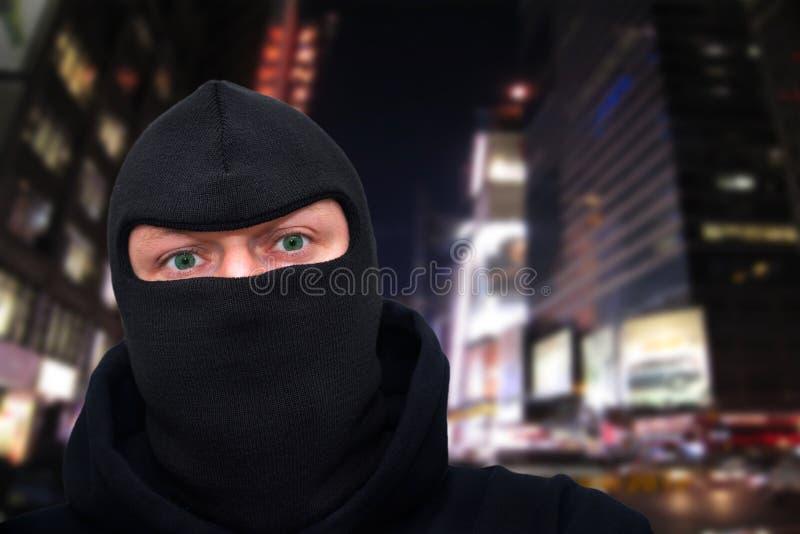 Hombre criminal con una máscara que se coloca en una calle en la noche imagen de archivo libre de regalías