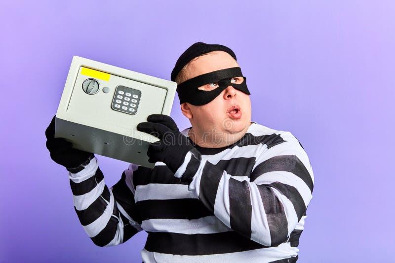 Hombre criminal del ladrón o del ladrón en la máscara que sostiene una caja fuerte a disposición para la rotura que la abre imagen de archivo libre de regalías