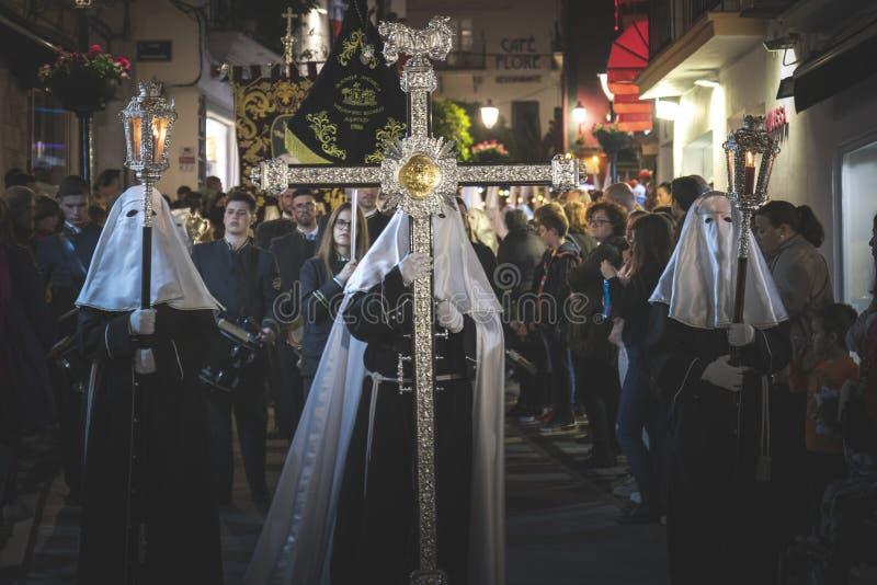 Hombre cruzado llevando la cruz en una procesión en la Semana Santa en Marbella foto de archivo