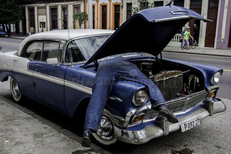 Hombre cubano con mitad de su cuerpo en el motor de 56 viejos Chevy imagenes de archivo