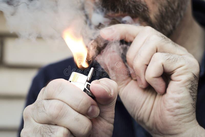 Hombre cubierto en cigarro de la iluminación del humo con un encendedor del metal fotografía de archivo libre de regalías
