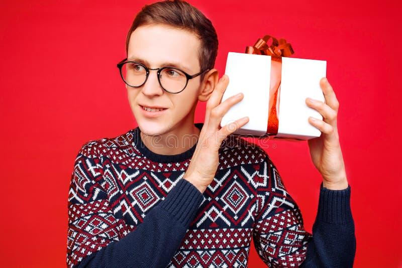 Hombre curioso con los vidrios, hombre que sostiene una caja de regalo, sacudiéndolo para descubrir cuál está dentro de la caja,  fotos de archivo