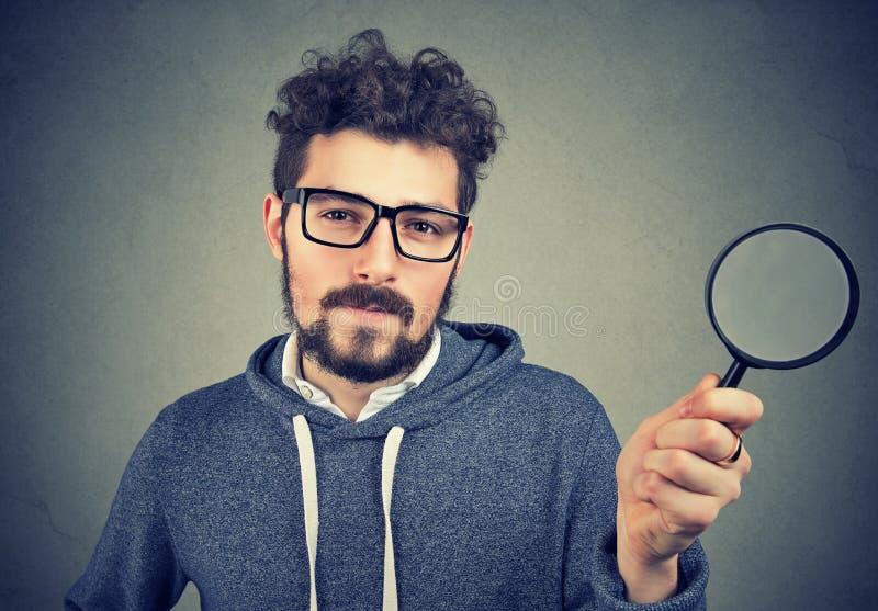 Hombre curioso que investiga con la lupa imágenes de archivo libres de regalías