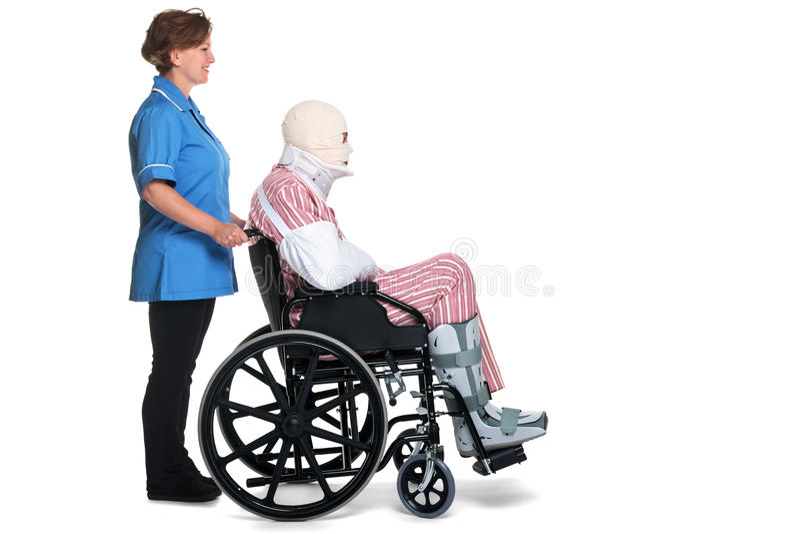 Hombre dañado en sillón de ruedas con empujar de la enfermera imagenes de archivo