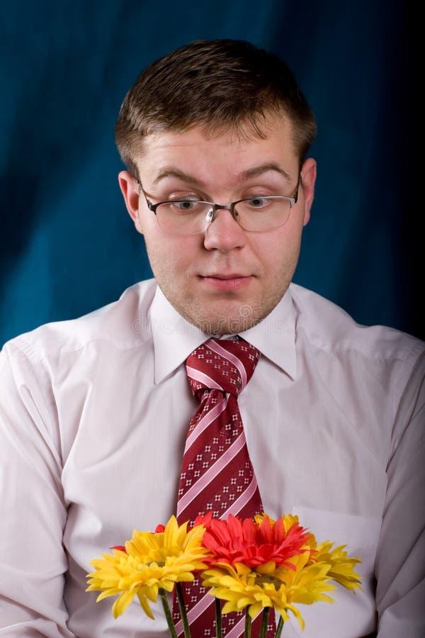 Hombre dado una sacudida eléctrica con las flores foto de archivo